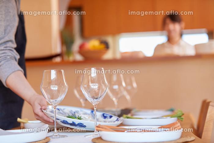 テーブルに料理を運ぶ男性