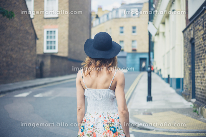 A young woman wearing a hat is walking in the street