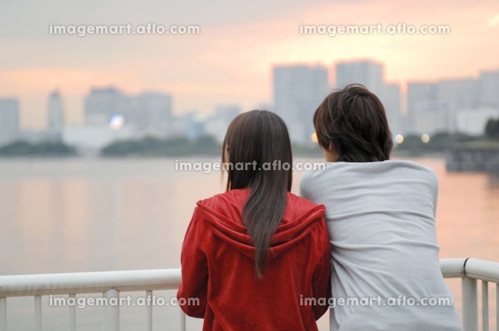 夕焼けを眺めるカップルの後姿の販売画像