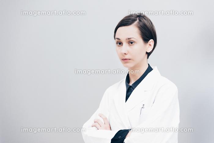 腕組みする白衣姿の若い女性の販売画像