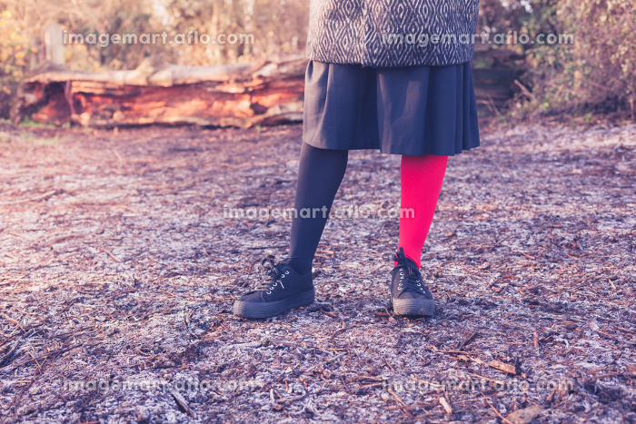 A young woman is wearing odd leggings and is standing on the frosty ground in a forest on a winter dayの販売画像
