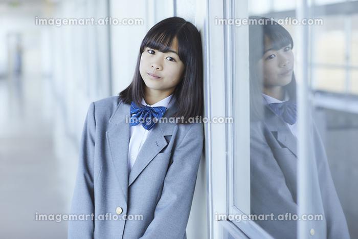 教室のドアにもたれかかる女子中学生