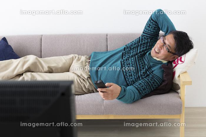 くつろいでテレビを見るミドル男性の販売画像