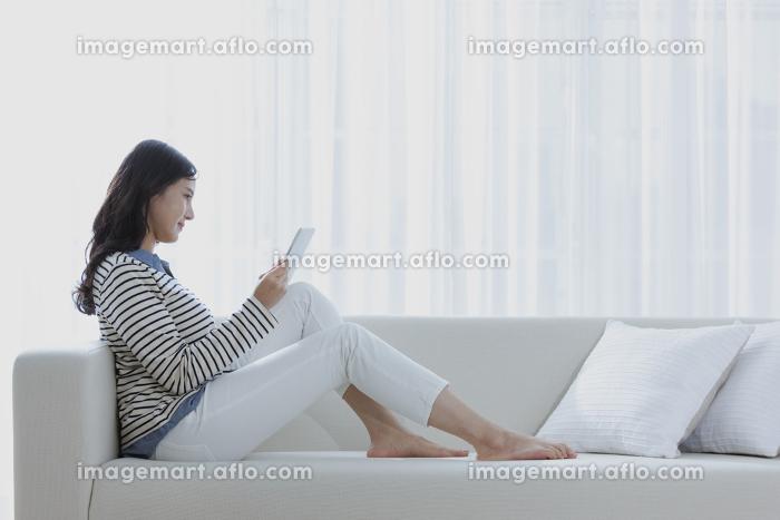 タブレットPCを見る女性の販売画像