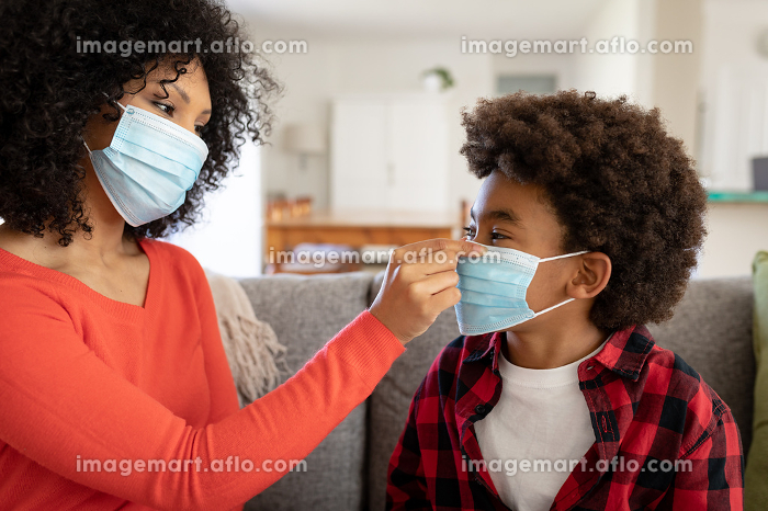 Mixed race mother with son enjoying family time together at home, social distancing and self isolation in quarantine lockdown, sitting on a couch, putting face masks onの販売画像