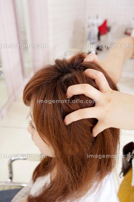 美容師にヘッドマッサージをしてもらう女性