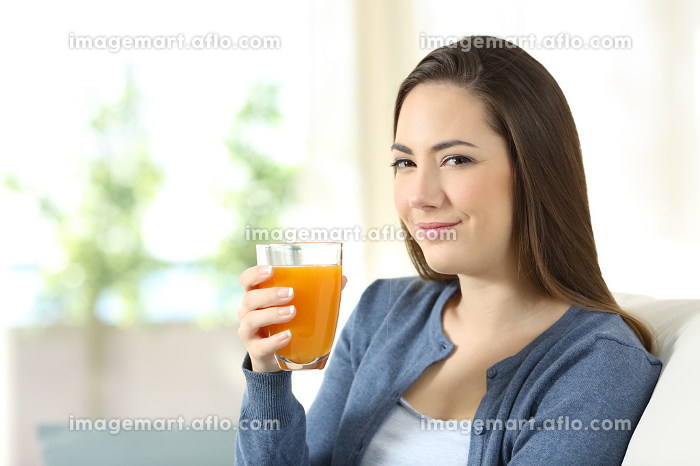 Serious woman holding a glass of orange juiceの販売画像