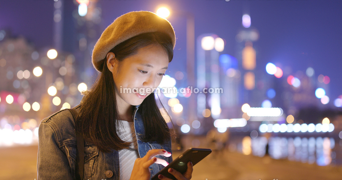 Woman look at smart phone in city at nightの販売画像