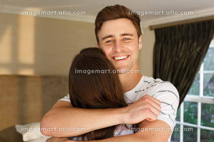 Caucasian couple embracing man smiling woman with back to camera. self isolation at home during covid 19 coronavirus pandemic.の販売画像
