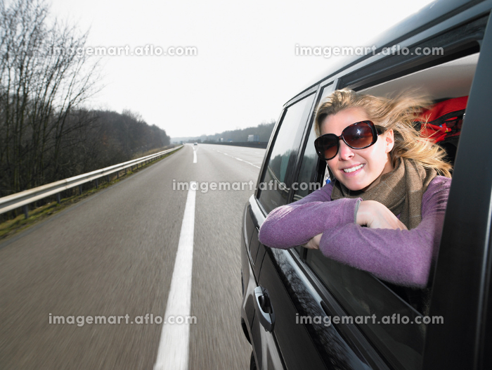 Young woman leaning out of car windowの販売画像