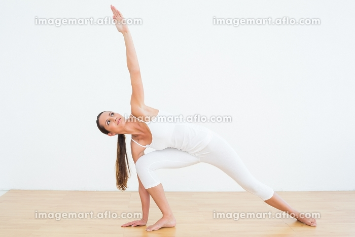 Full length of a fit young woman doing pilate exercises in the fitness studioの販売画像
