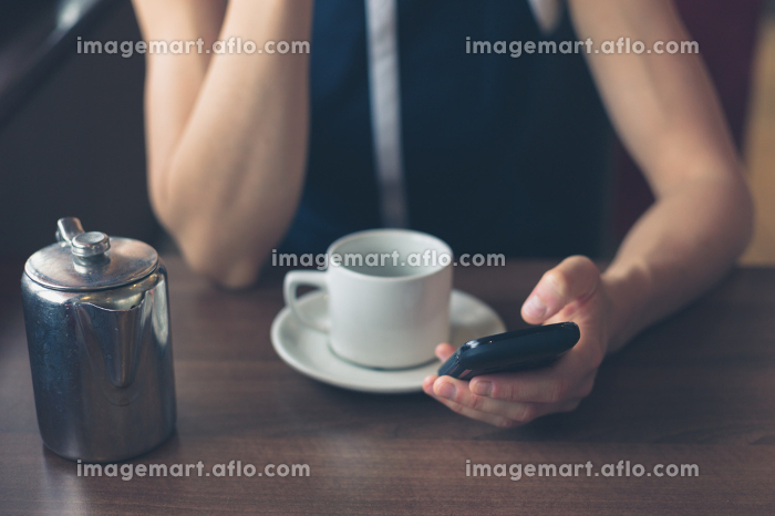 A young woman is having a cup of coffee in a diner and is using her smartphoneの販売画像