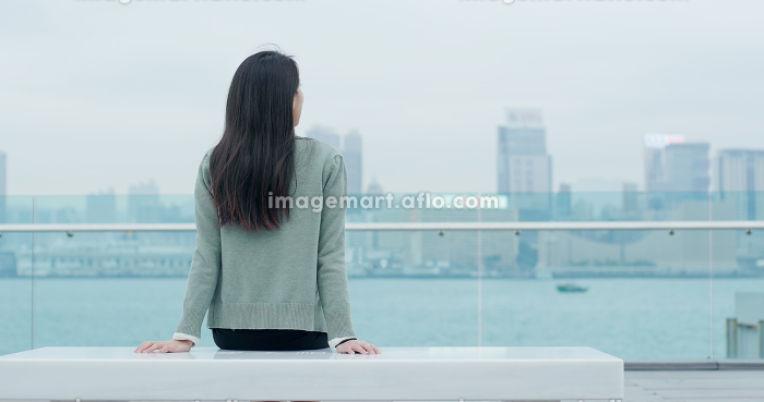 Woman sitting at the bench and looking at the view in Hong Kongの販売画像