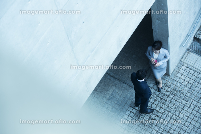 会話をするビジネスマンとビジネスウーマンの斜俯瞰の販売画像