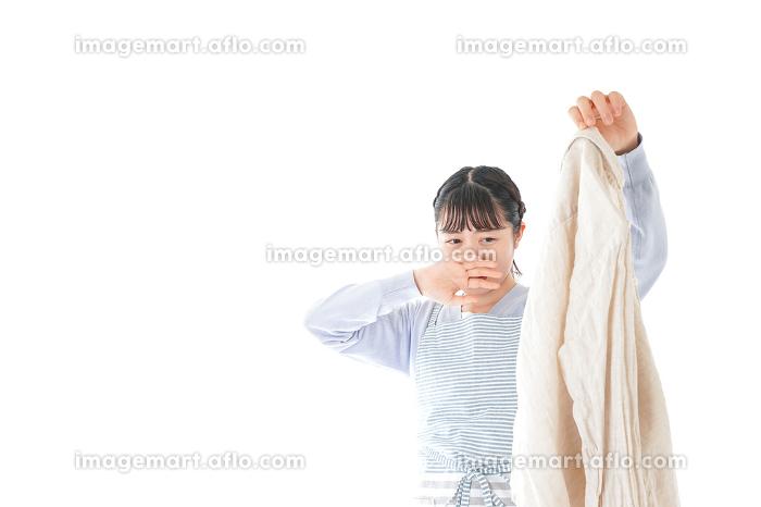 洗濯物を臭う若い女性の販売画像