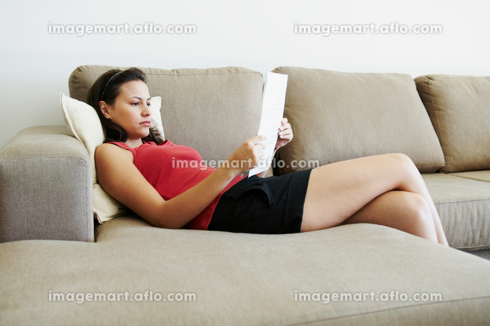 Reclined woman reading paperworkの販売画像