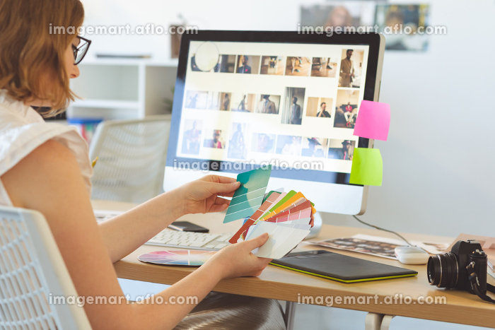 Rear view of young Caucasian graphic designer checks the color with color swatch at desk in officeの販売画像