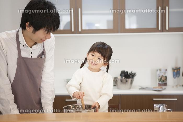 父親と一緒に料理をする笑顔の女の子