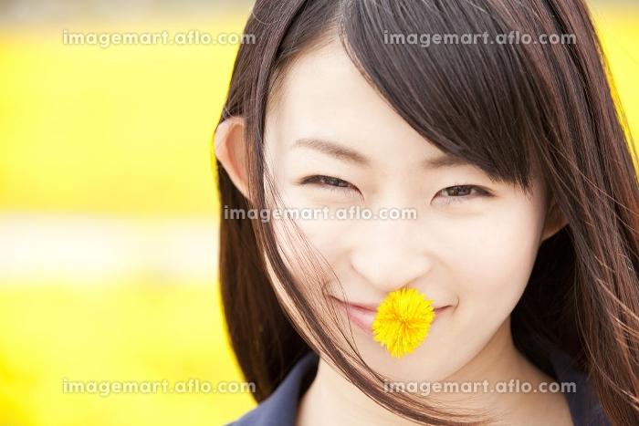 タンポポを口にくわえて微笑む女性