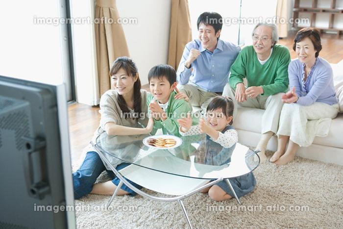 リビングでテレビを見る家族の販売画像