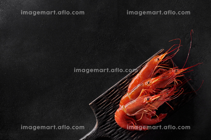 Top view of cooked whole prawns on black backgroundの販売画像