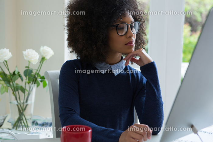 Thoughtful woman working on desktop pc at deskの販売画像