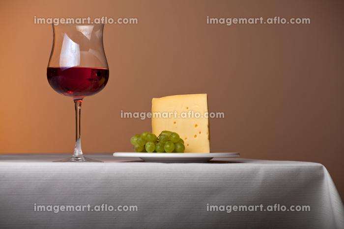 テーブルの上の赤ワインとチーズと葡萄の販売画像