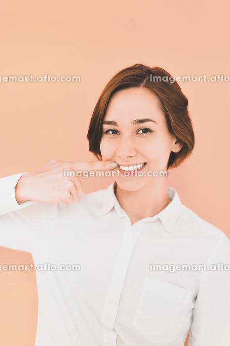 口を指差す若い女性(デンタルイメージ)の販売画像