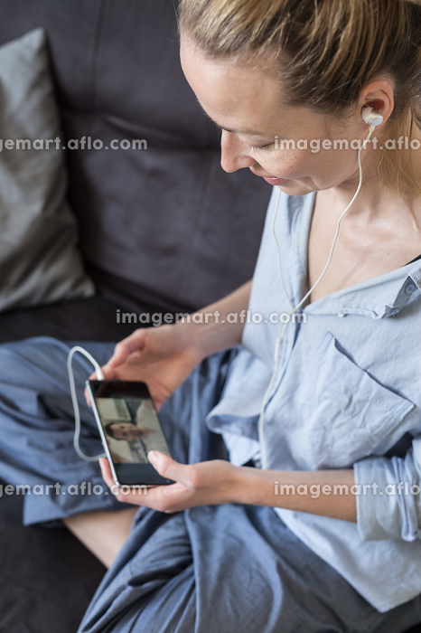 Woman at home relaxing on sofa couch using social media on phone for video chatting with her loved ones during corona virus pandemic. Stay at home, social distancing lifestyle.の販売画像