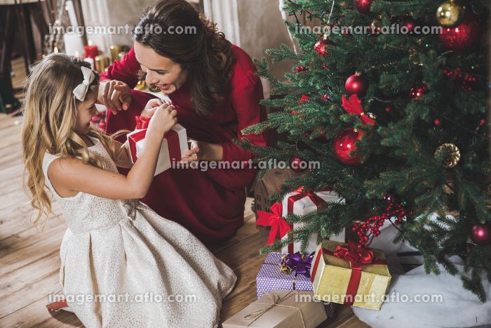Mother giving daughter Christmas presentの販売画像