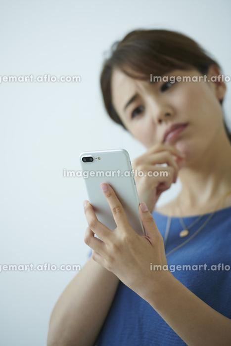 スマートフォンを見て首をかしげる日本人女性