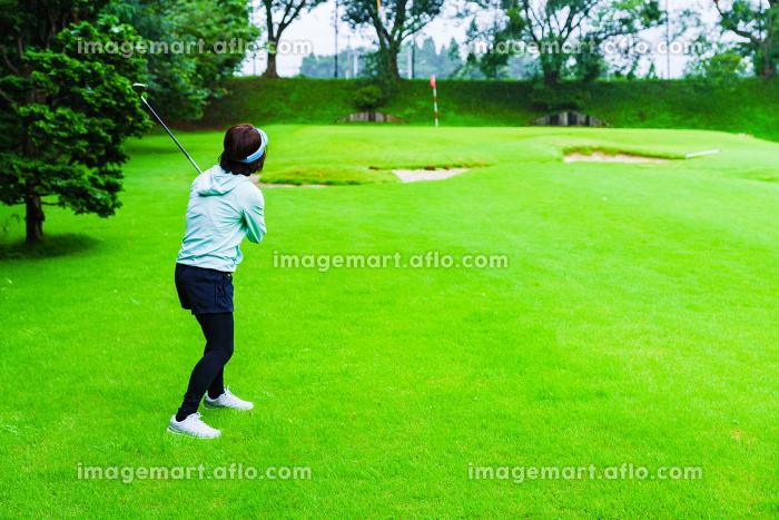 雨天にゴルフをする女性 【コロナ禍で楽しめるスポーツ】の販売画像