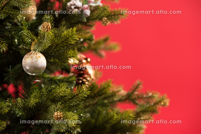 Christmas Tree on red background decorated with golden balls toys and bowsの販売画像