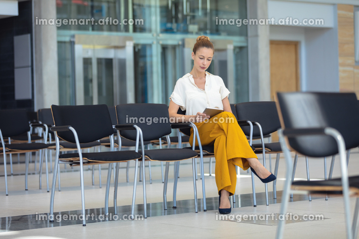 Front view of young Caucasian female executive looking at digital tablet while sitting on chair in empty conference roomの販売画像