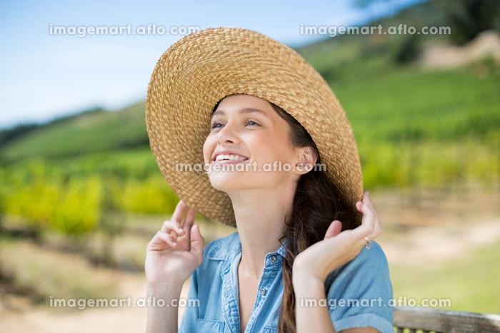 Happy woman wearing sun hat while looking awayの販売画像