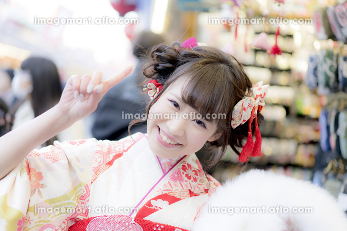 参道でお土産を物色する振袖の女性の販売画像