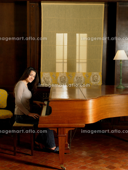 Young woman playing piano smiling