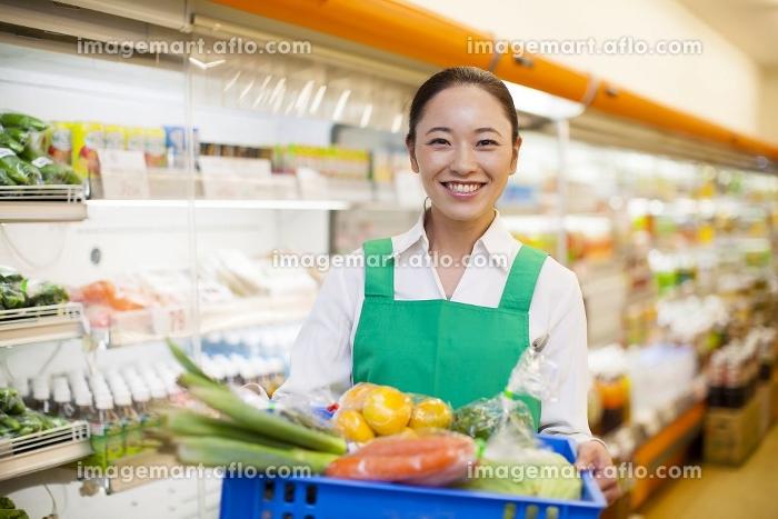 野菜の入った箱を持つ女性店員