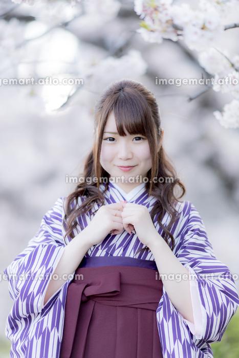 桜の前で胸に手を当てる袴の女性の販売画像