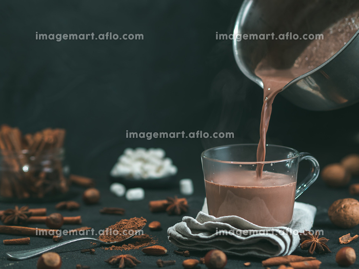 Pouring tasty cocoa drink into mug on table