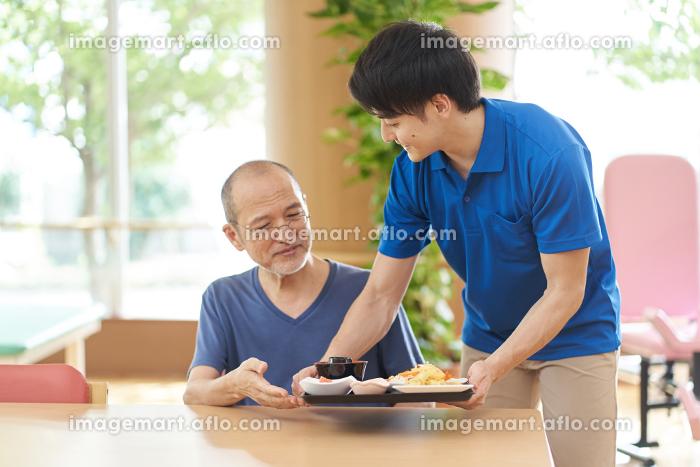 高齢者に配膳をする介護士の販売画像