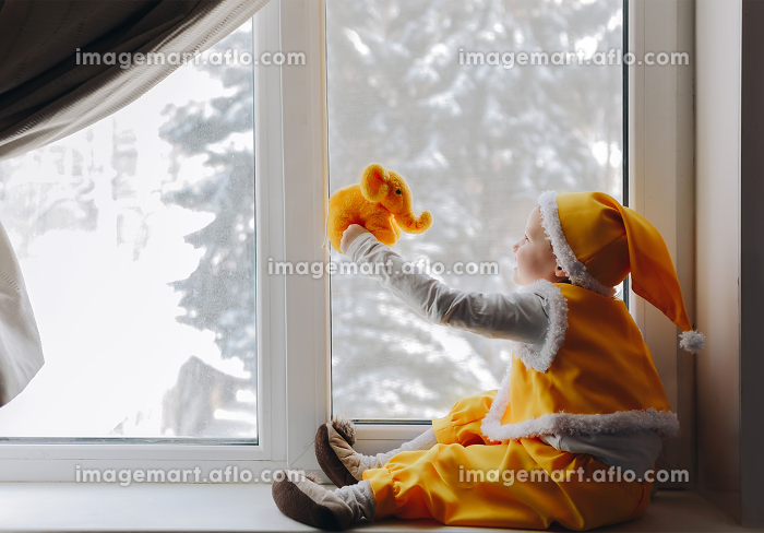 Little boy in yellow elf gnome costume sit at windowsill with elephantの販売画像
