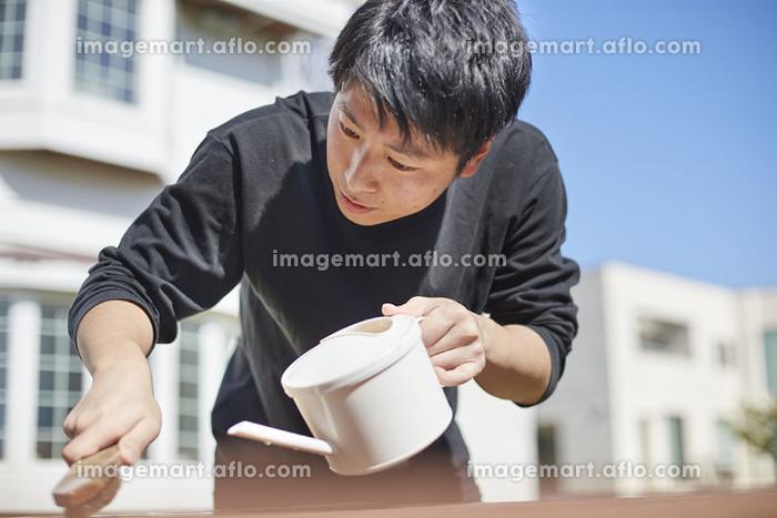 テーブルの汚れを取る日本人男性の販売画像