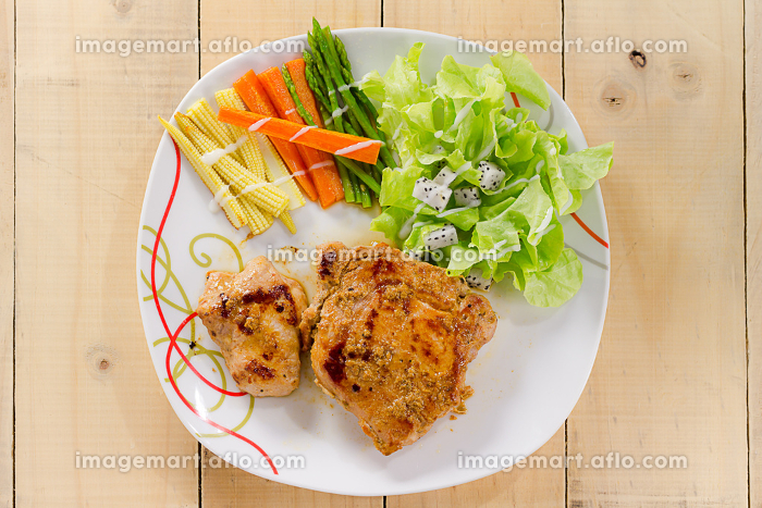 Grilled steaks on dish with saladの販売画像