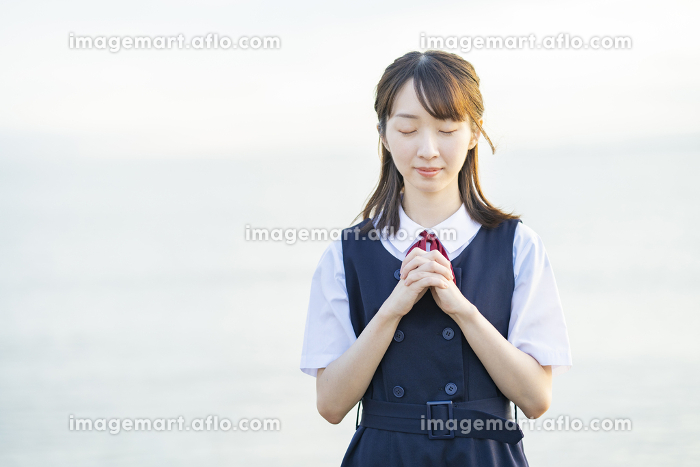 お祈りをするアジア人女性の高校生の販売画像