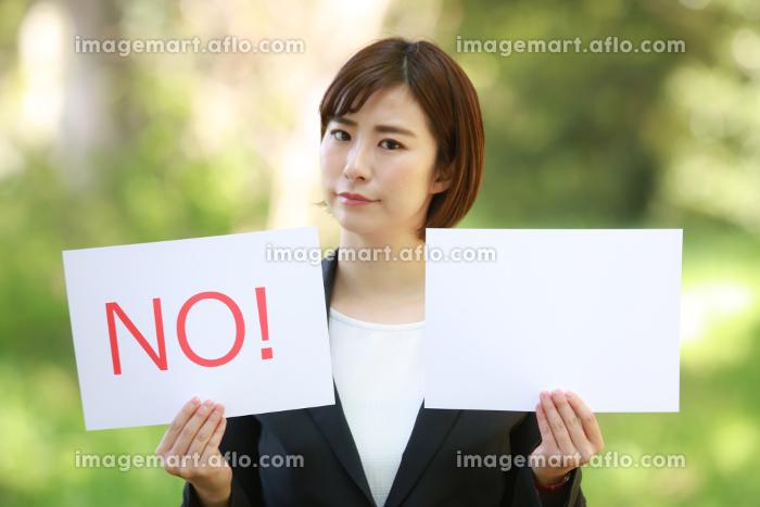 「NO!」と書かれたメッセージボードと無地のメッセージボードを持つ女性社員の販売画像