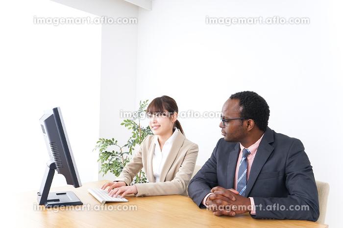 オフィスでパソコンを使う会社員の販売画像