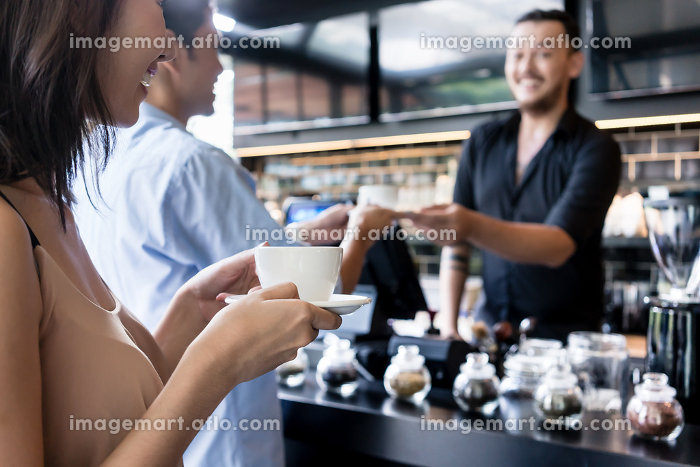 Young woman holding a white cup of coffee next to her partnerの販売画像