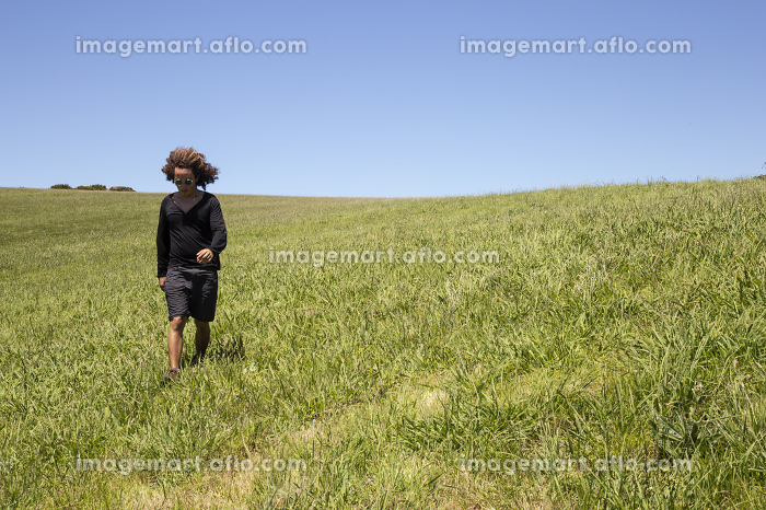 Man with curly hair walking on green grassland under blue sky, Waiheke