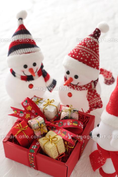 クリスマスに箱いっぱいに積んだプレゼントを運んでくるゆきだるま達と雪景色の販売画像